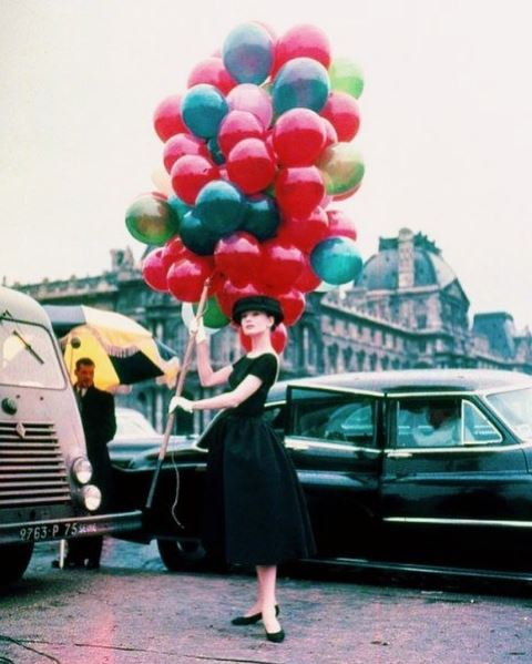 Audrey Hepburn dressed in black dress holding a large number of balloons of different colours with some classic cars in the background