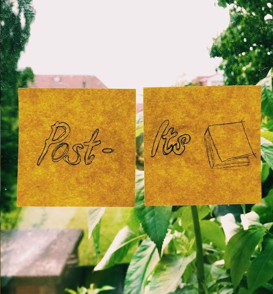 two yellow post it notes stuck to a window. One has the word 'post' on it while the other has the word 'its; with a sketch of a pad of post its