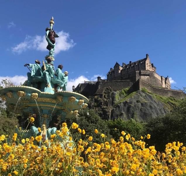 Edinburgh castle in background, fountain and yellow flowers in foreground